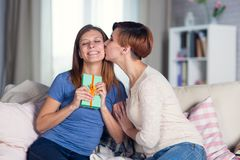 Homosexual couple of lesbian women at home on the couch celebrat. Homosexual couple of lesbian women at home on the couch kisses on the cheek celebrating a Royalty Free Stock Photography