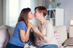 Homosexual couple of lesbian women at home on the couch celebrat. Homosexual couple of lesbian women at home on the couch kisses on the lips celebrating a Royalty Free Stock Photography