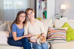 Homosexual couple of lesbian women at home on the couch. With a redheaded pet cat Royalty Free Stock Images