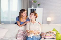 Homosexual couple of lesbian women at home on the couch. With a redheaded pet cat Royalty Free Stock Image