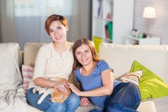 Homosexual couple of lesbian women at home on the couch. With a redheaded pet cat Royalty Free Stock Photography