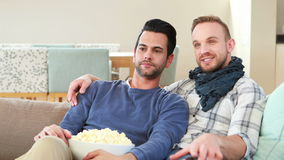 Homosexual couple men eating popcorn together. On sofa stock footage