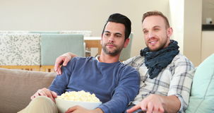 Homosexual couple men eating popcorn together. On sofa stock video