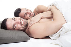 A homosexual couple onder a bed in studio white Stock Photography
