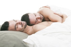 A homosexual couple onder a bed in studio white Royalty Free Stock Image