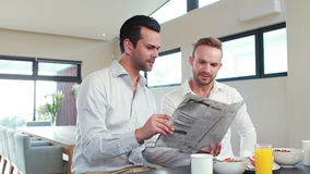 Homosexual couple reading newspaper in the kitchen. At home stock footage