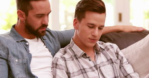 Homosexual couple reading on the sofa stock video