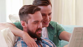 Homosexual couple speaking and reading newspaper. Homosexual couple speaking reading newspaper in the living room stock video footage