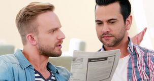 Homosexual couple speaking and reading newspaper. In living room stock video