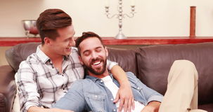 Homosexual couple together on the sofa. Homosexual couple on the sofa in the living room stock footage