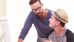 Homosexual couple using tablet. In the office stock video