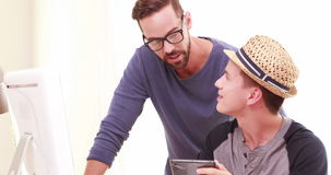 Homosexual couple using tablet. In the office stock footage