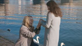 Lesbian girl proposing about marriage. A homosexual female couple celebrating the engagement. Same-sex partners feeling
