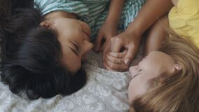 Homosexual mixed race lesbian couple lying on bed, looking each other. Two women sharing love and support holding hands