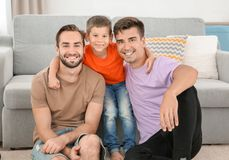 Homosexual male couple with foster son at home. Adoption concept Royalty Free Stock Images