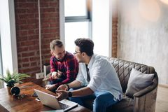 Homosexual partners working at office desk, relationships and business concept. Business male couple working together on project at modern start up office with royalty free stock image