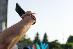 Homosexual young man with rainbow wristband, bracelet and smart phone taking selfie in Pride festival. Lifestyle, fun, guy, flag, gay, attractive, portrait royalty free stock image