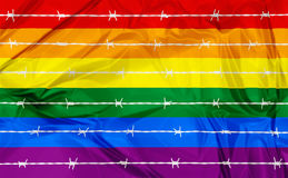 Homosexuality and Homophobia. Conceptual illustration of a rainbow flag symbol of pride and freedom homosexual in background and above a row of barbed wire Stock Photography