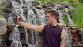 Homosexueel die selfie dichtbij waterval nemen Mens het stellen voor selfiefoto openlucht stock video