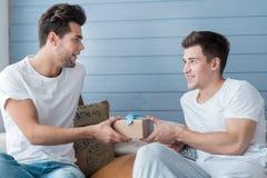 Homosexuel de sourire gai présent un cadeau à son ami Images stock