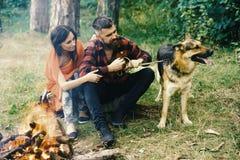 Homosexuel doux Miel Couplez le jeu avec le chien de berger allemand près du feu, fond de forêt Image stock