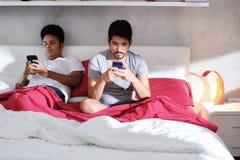 Homosexuelle Männer mit Smartphones ignorierend lizenzfreie stockfotos