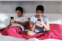 Homosexuelle Männer mit Smartphones ignorierend stockbilder