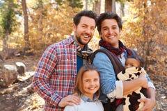Homosexuelle männliche Paare mit den Kindern, die durch Fall-Waldland gehen Stockfotos