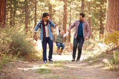 Homosexuelle männliche Paare mit der Tochter, die durch Fall-Waldland geht Stockfotos