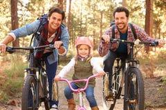 Homosexuelle männliche Paare mit der Tochter, die durch Fall-Waldland radfährt Lizenzfreie Stockfotos