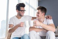 Homosexuelle Paare, die ein heißes Getränk zusammen haben lizenzfreies stockfoto