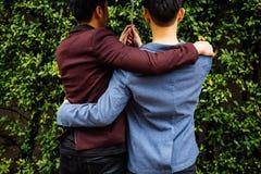 Homosexuelle Paare, die Regenschirm und Hände zusammenhalten Zurück von den homosexuellen Männern, die in den Regen gehen lizenzfreies stockbild
