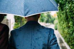 Homosexuelle Paare, die Regenschirm und Hände zusammenhalten Zurück von den homosexuellen Männern, die in den Regen gehen lizenzfreie stockfotos