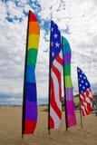 Homosexuelle Stolzmarkierungsfahnen des Amerikaners und des Regenbogens auf dem Strand Stockfotografie