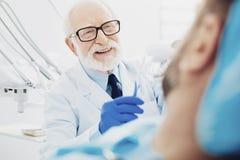 Homosexueller männlicher Zahnarzt, der das Zahnsäubern anzeigt stockbilder