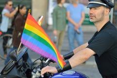 Homosexueller Mann auf seinem Motorrad mit Regenbogenflagge Lizenzfreie Stockfotografie