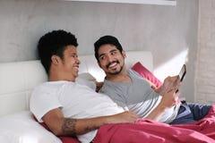 Homosexueller Mann, der Video mit Partner im Bett spielt lizenzfreies stockbild