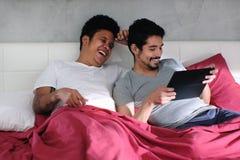 Homosexueller Mann, der Video mit Partner im Bett spielt lizenzfreie stockbilder