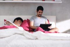 Homosexueller Mann, der Videospiel mit dem Partner-Schlafen spielt stockfotografie