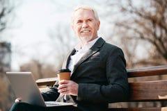 Homosexueller reifer Geschäftsmann, der im Park schreibt stockfotografie