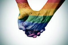 Homosexuelles Paarhändchenhalten, kopiert als die Regenbogenflagge Stockfotografie