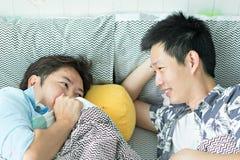 A homossexualidade dos pares relaxa na cama no quarto imagens de stock royalty free