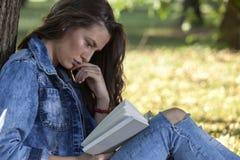 Hon älskar för att läsa en bok och för att koppla av i natur Royaltyfri Fotografi