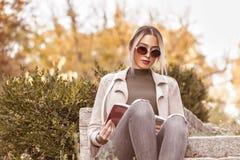 Hon älskar för att läsa en bok och för att koppla av utomhus arkivfoton
