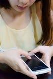 Hon använder en mobiltelefon Arkivbild