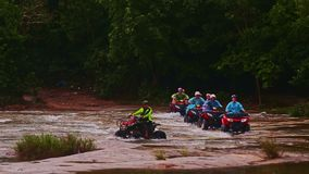 Tourists Drive All Terrain Vehicles across River against Jungle stock video