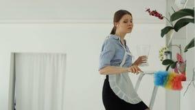 Hon gör ren dammet i hotellet och dansen stock video