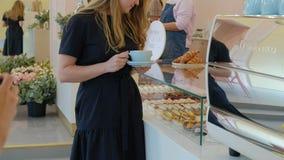 Hon köparen väljer smaskigt Ung attraktiv flicka, kvinnabuys i coffee shop eller bakelser, kakor, kaka, makron A arkivfilmer