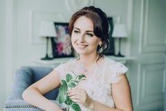 Hon ler och rymmer en ros i henne händer arkivfoto