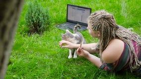 Hon matar katten utomhus Arbete bak bärbara datorn lager videofilmer